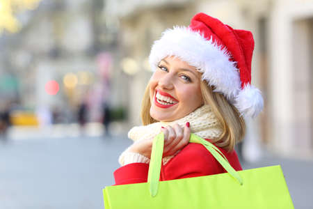 Portrait of a happy woman weating a santa claus hat shopping in christmas looking at you outdoors on the street