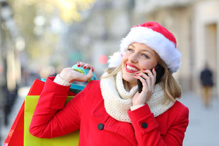 Happy shopper in red holding shopping bags talking on phone on christmas holidays on the street