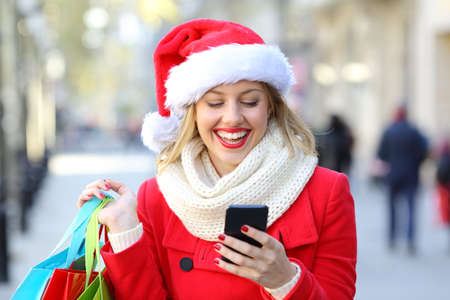 Front view portrait of a happy shopper holding shopping bags checking phone on christmas in the street