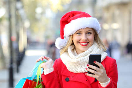 Front view portrait of a happy shopper shopping online looking at camera on christmas holidays on the street