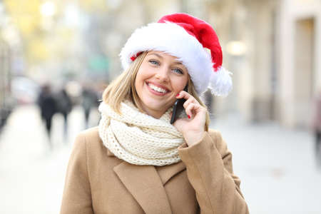 Happy woman talking on phone looking at you in christmas in the street