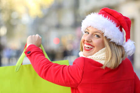 Portrait of a happy woman shopping in christmas wearing a santa claus hat outdoors on the street