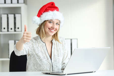 Happy employee with thumbs up at office looking at camera in christmas