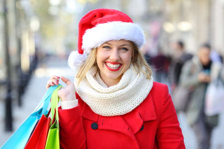 Front view portrait of a happy shopper holding shopping bags posing in the street on chritmas holidays