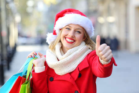 Satisfied shopper hoolding shopping bags with thumbs up on christmas in the street Stock Photo