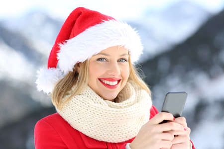 Portrait of a lady on christmas holidays holding a smart phone with a snowy mountain in the background