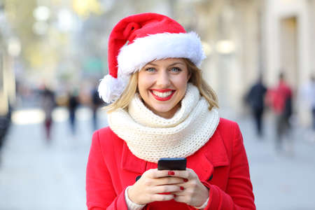 Front view portrait of a happy woman holding a phone looking at you on christmas in the street Stock Photo - 108938615