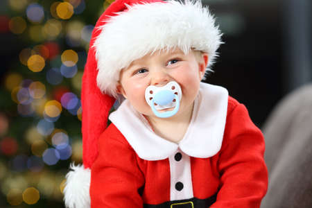 Baby wearing santa disguise with a pacifier in the mouth looking at camera in christmas on a couch in the living room at home
