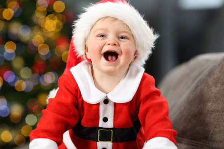 Joyful child wearing santa claus disguise on a couch at home in christmas with a tree in the background