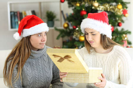 Disappointed woman receiving a gift from a frustrated friend in christmas at home
