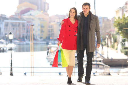 Front view full body portrait of a happy couple of tourists shopping on winter vacation holding bags