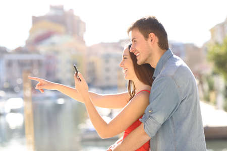 Side view portrait of a happy couple checking a smart phone pointing away on vacation