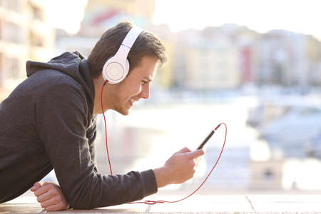 Side view portrait of a teenage boy listening to music with phone and headphones