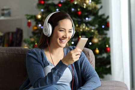 Happy girl wearing headphones listening to music in christmas sitting on a couch in the living room at home