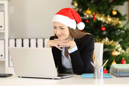 Satisfied office worker reading on line content in a laptop in christmas