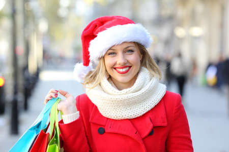 Front view portrait of a happy shopper looking at you on christmas in the street