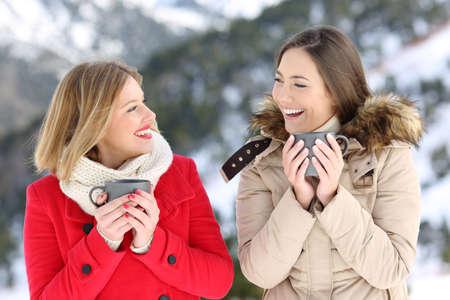 Two happy women talking holding coffee cups in winter holiday in the mountain Foto de archivo - 109772742