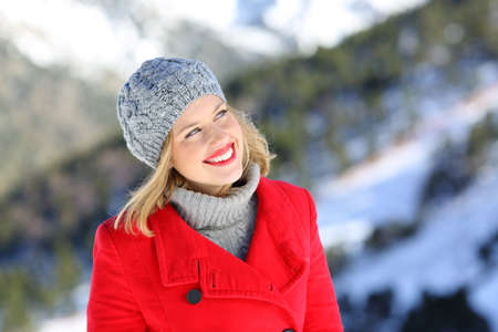 Front view portrait of a happy woman in red thinking looking at side in winter holiday in the mountain Stock Photo