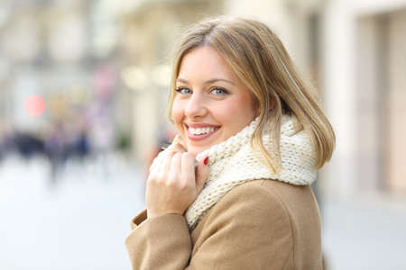 Portrait of a happy woman posing looking at camera in winter in the street