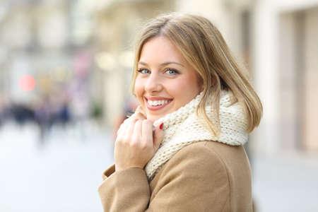 Ritratto di una donna felice in posa guardando la fotocamera in inverno in strada Archivio Fotografico - 109772752