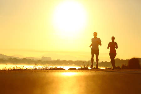 Man and woman silhouettes running at sunrise in a coast road Stockfoto