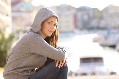 Portrait of a confident teenager girl looking at camera in a coast town Stok Fotoğraf