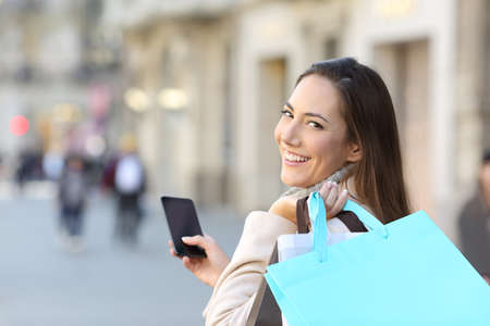 Happy shopper holding a smart phone and blank shopping bags walking in the street