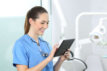 Happy dentist consulting online information in a tablet in a consultation Banco de Imagens