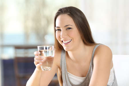 Happy woman posing holding a glass of water at home Foto de archivo - 109800610