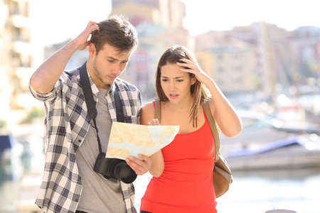 Lost confused couple of tourists looking at a paper map on vacation in a coast town