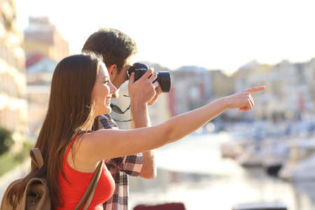 Two happy tourists sightseeing and taking photos with a dslr camera outdoors on vacation