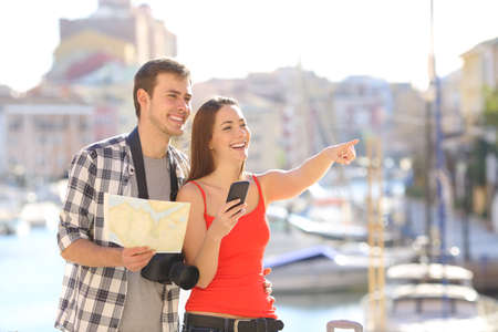 Couple of tourists traveling on vacation sightseeing pointing at landmarks