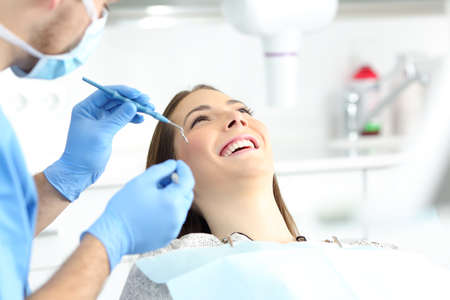 Happy woman with perfect smile in a dentist office ready to treatment