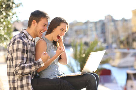 Excited couple on vacation watching online content in a laptop in a sunny day