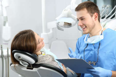 Young dentist explaining dental treatment procedure to a patient in a consultation Фото со стока