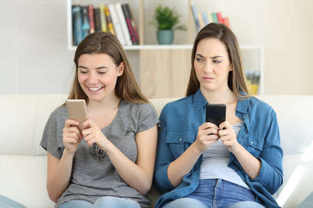 Envious woman looking at her friend texting in a phone sitting on a couch in the living room at home