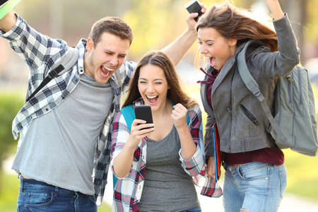 Three excited students checking exam grades online in a smart phone