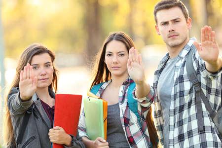 Tre studenti arrabbiati che gesticolano si fermano in un parco Archivio Fotografico - 109890200