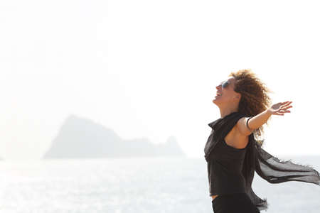 Side view portrait of a happy woman breathing on the beach with an island in the background