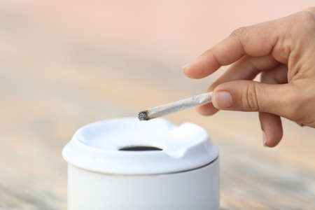Close up of a woman smoking holding a hand made cigarette throwing the ash into the ashtray