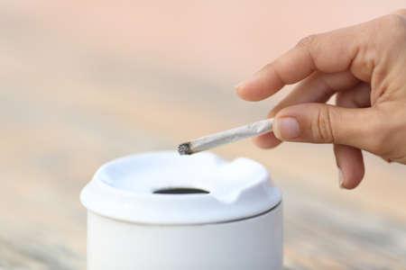 Primo piano di una donna che fuma tenendo una sigaretta fatta a mano gettando la cenere nel posacenere