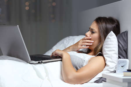 Worried woman finding bad news in a laptop on the bed in the night at home