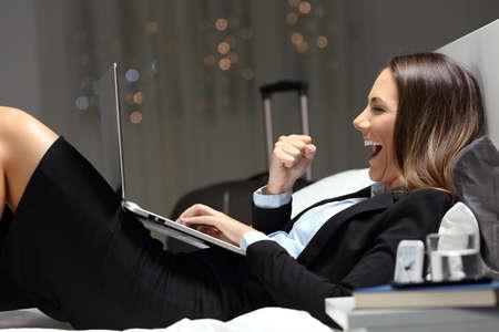 Bussinesswoman emocionada durante un viaje de negocios para encontrar contenido en línea en una computadora portátil acostada en una cama en la habitación del hotel Foto de archivo