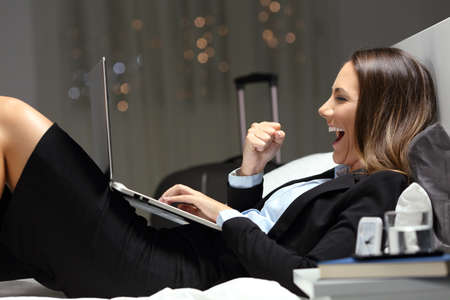 Excited bussinesswoman during a business travel finding online content in a laptop lying on a bed at hotel room Stock Photo