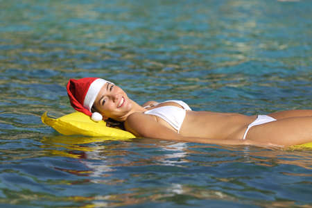 Happy woman enjoying on the beach floating in a transparent tropical water on christmas holiday Фото со стока