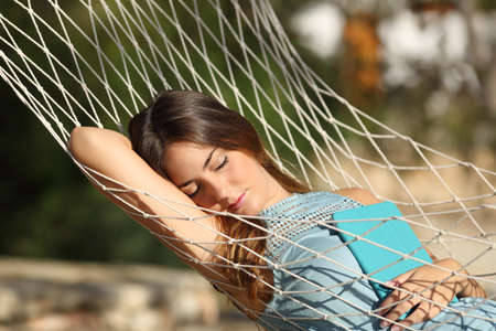 Happy relaxed woman sleeping on a hammock holding a tablet on vacation