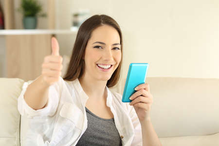 Happy woman holding a phone with thumbs up sitting on a couch in he living room at home