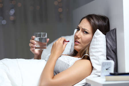 Ill woman complaining and taking pill looking at camera lying in the night at home