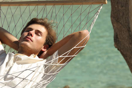 Man relaxing resting on a hammock on vacation with a turquoise sea in the background Stock Photo