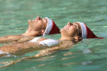 Heureux couple portant des chapeaux de père Noël flottant sur une plage tropicale pendant les vacances de Noël